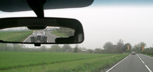 Look in the mirror and catch this antique car driving on the left in the English Countryside.
